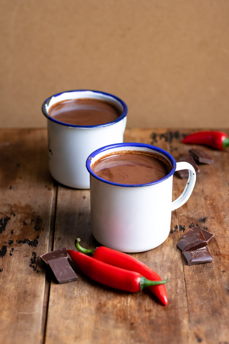 Table with two mugs of hot chocolate and chili peppers and chocolate on the table.