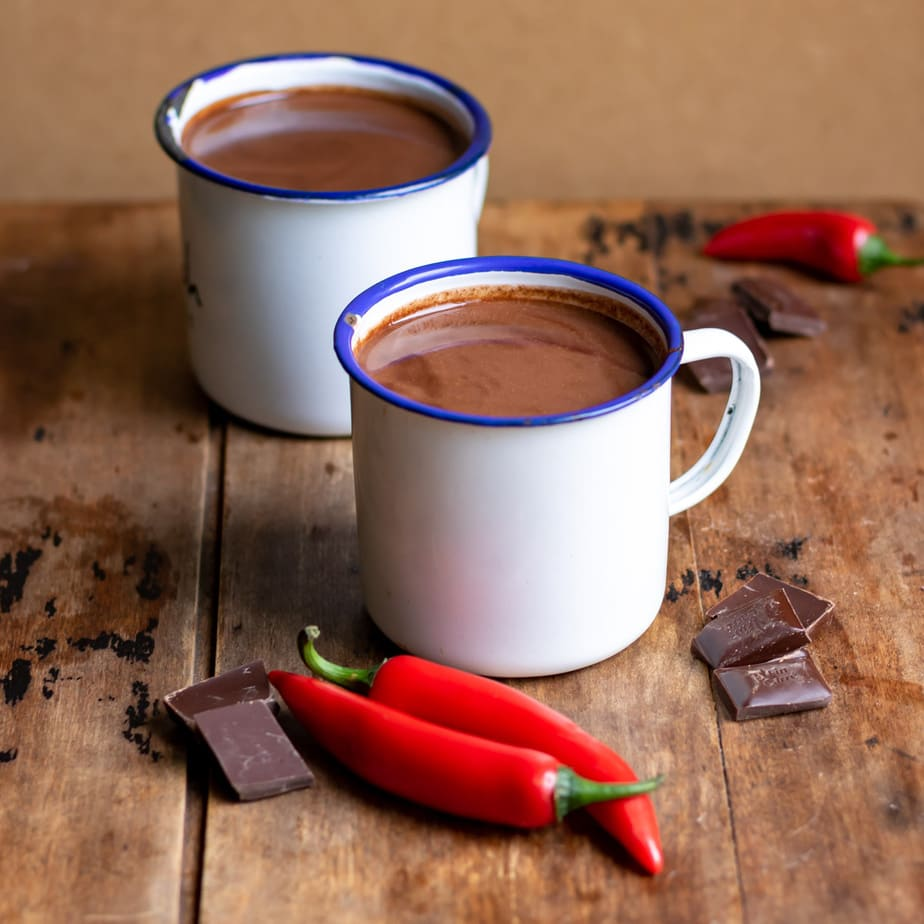 Table with two mugs of hot chocolate and chili peppers and chocolate nearby.