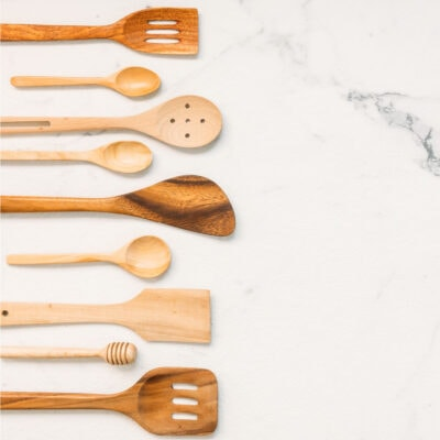 Wooden kitchen utensils on marble.