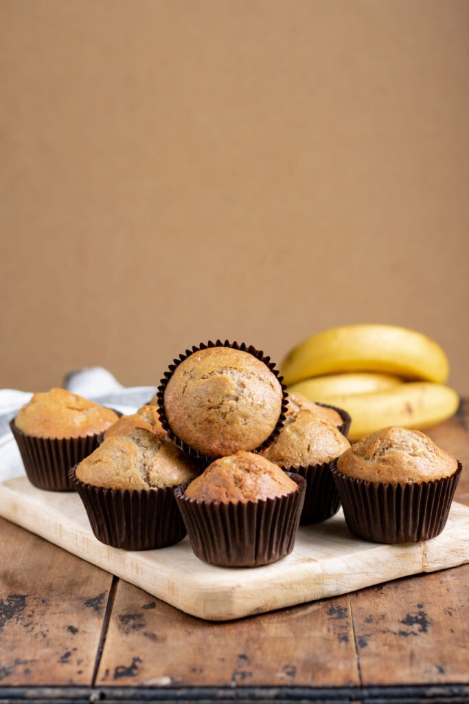 Muffins on a board on a table.