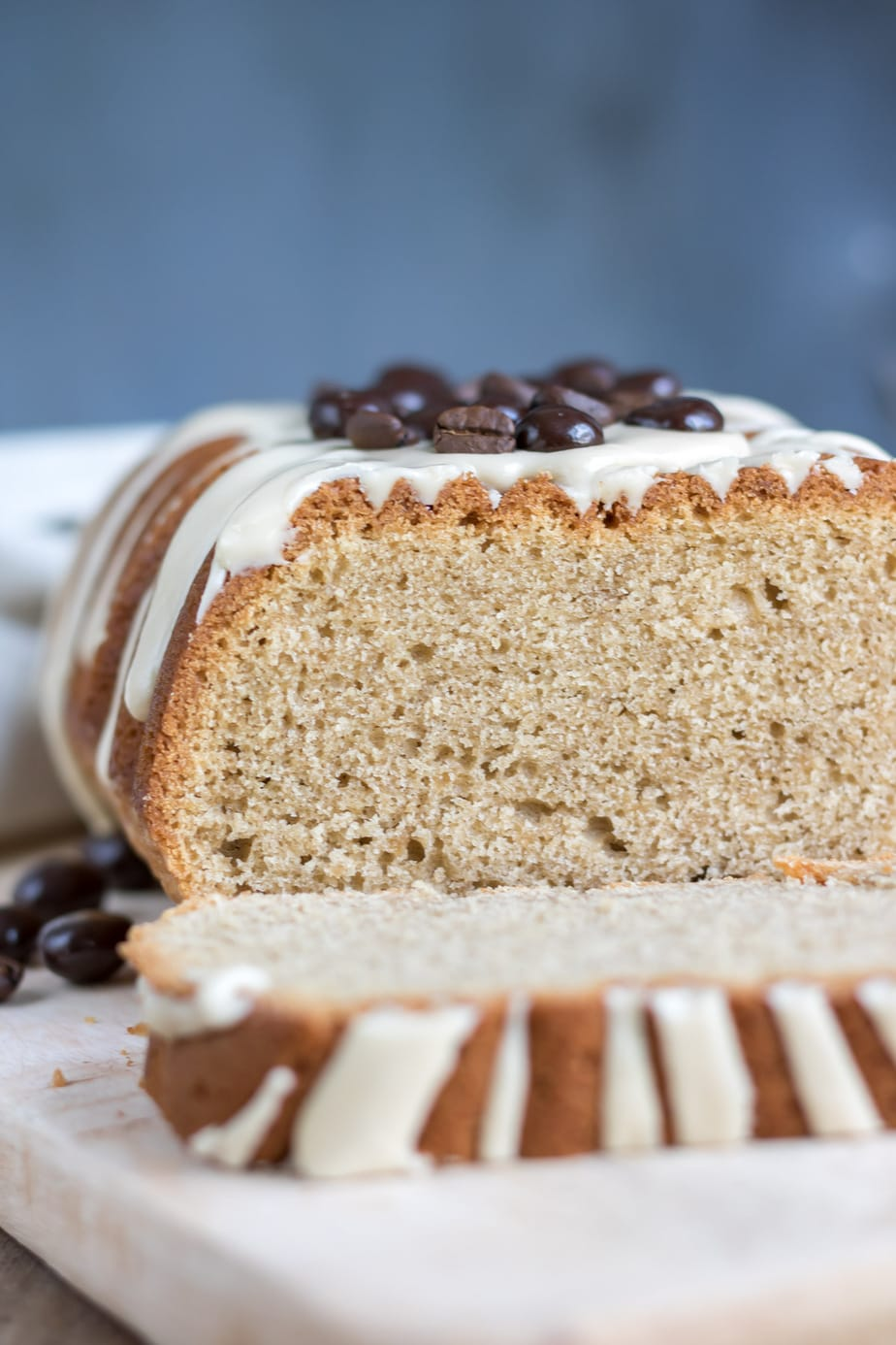 Close up of a loaf cake with a slice laying down.