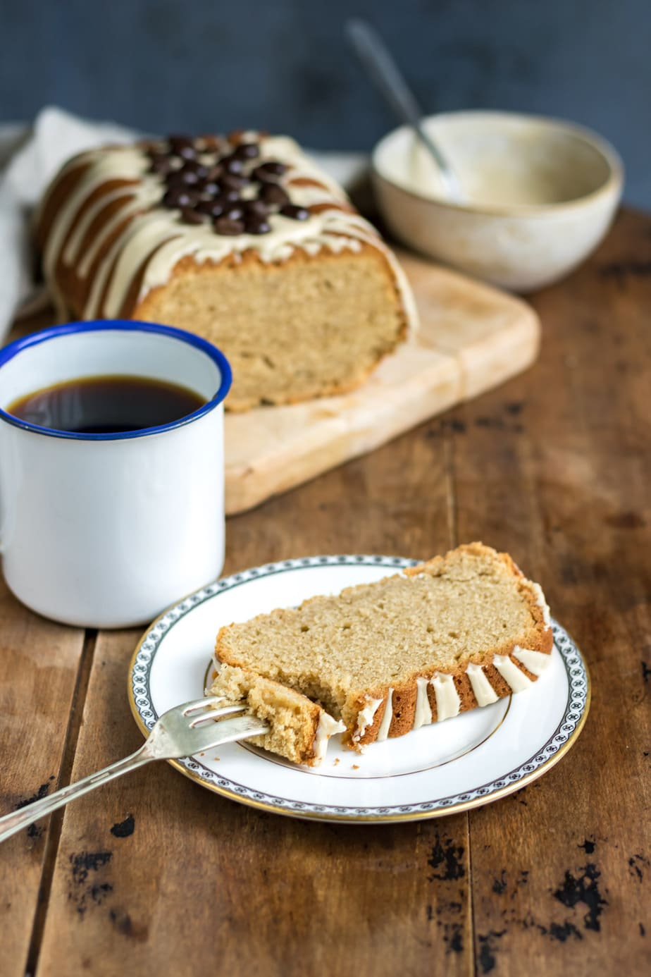 Slice of loaf cake on a plate, next to a coffee and the rest of the cake.