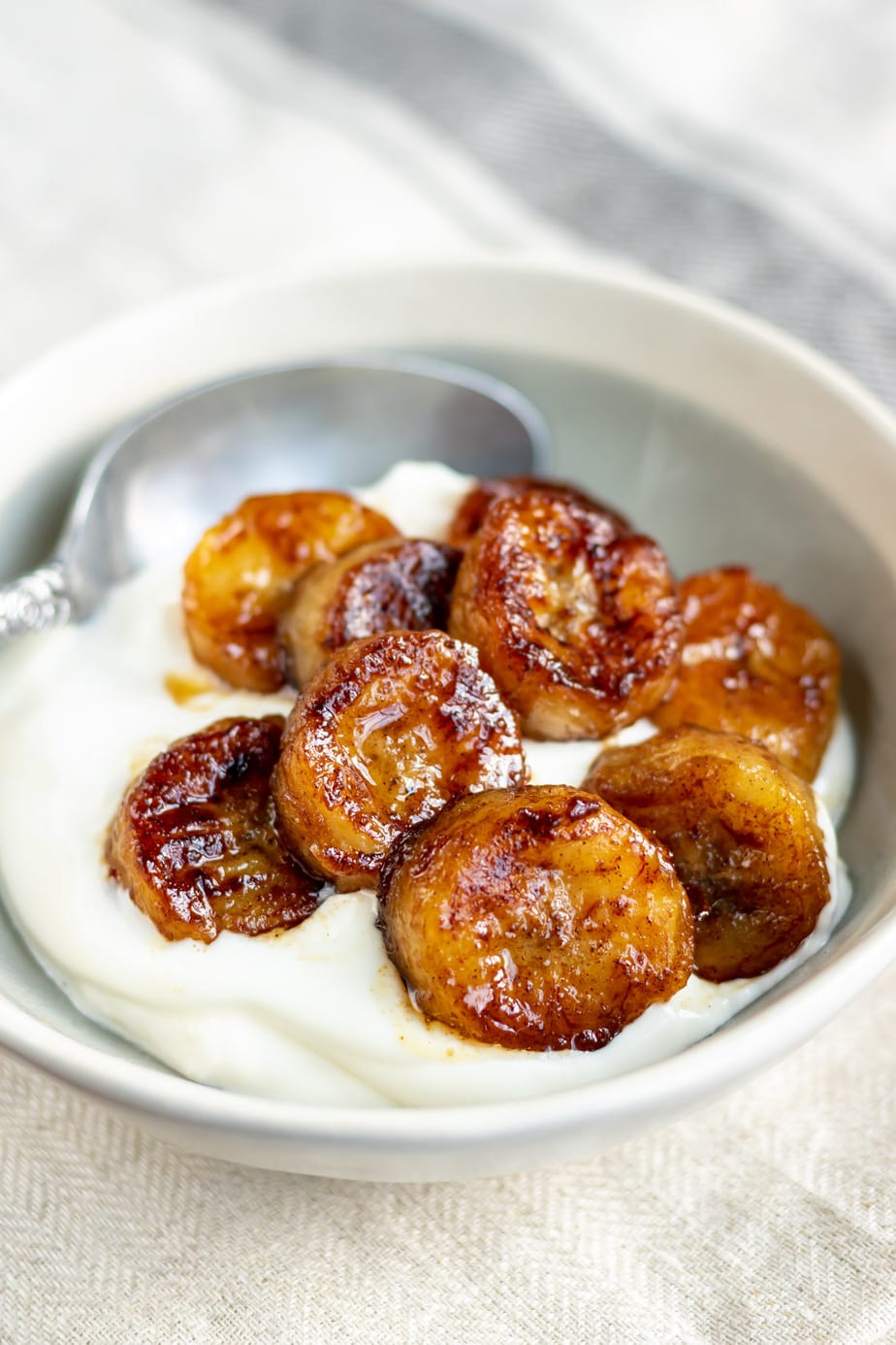 Bowl of yogurt topped with banana slices that have been fried in maple syrup.