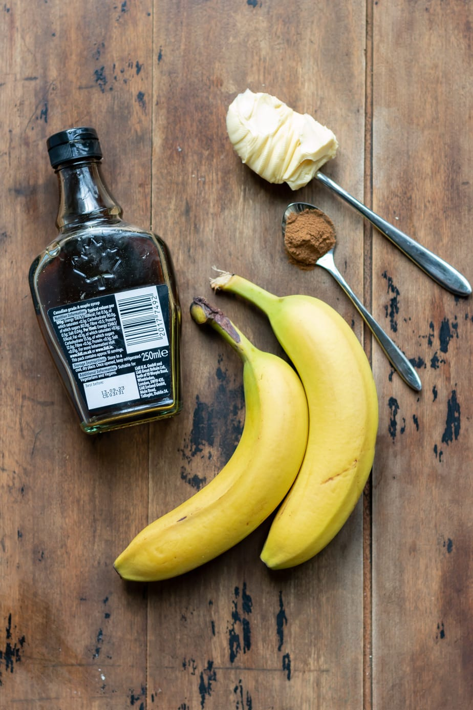 Maple syrup, bananas, cinnamon and butter on a table.