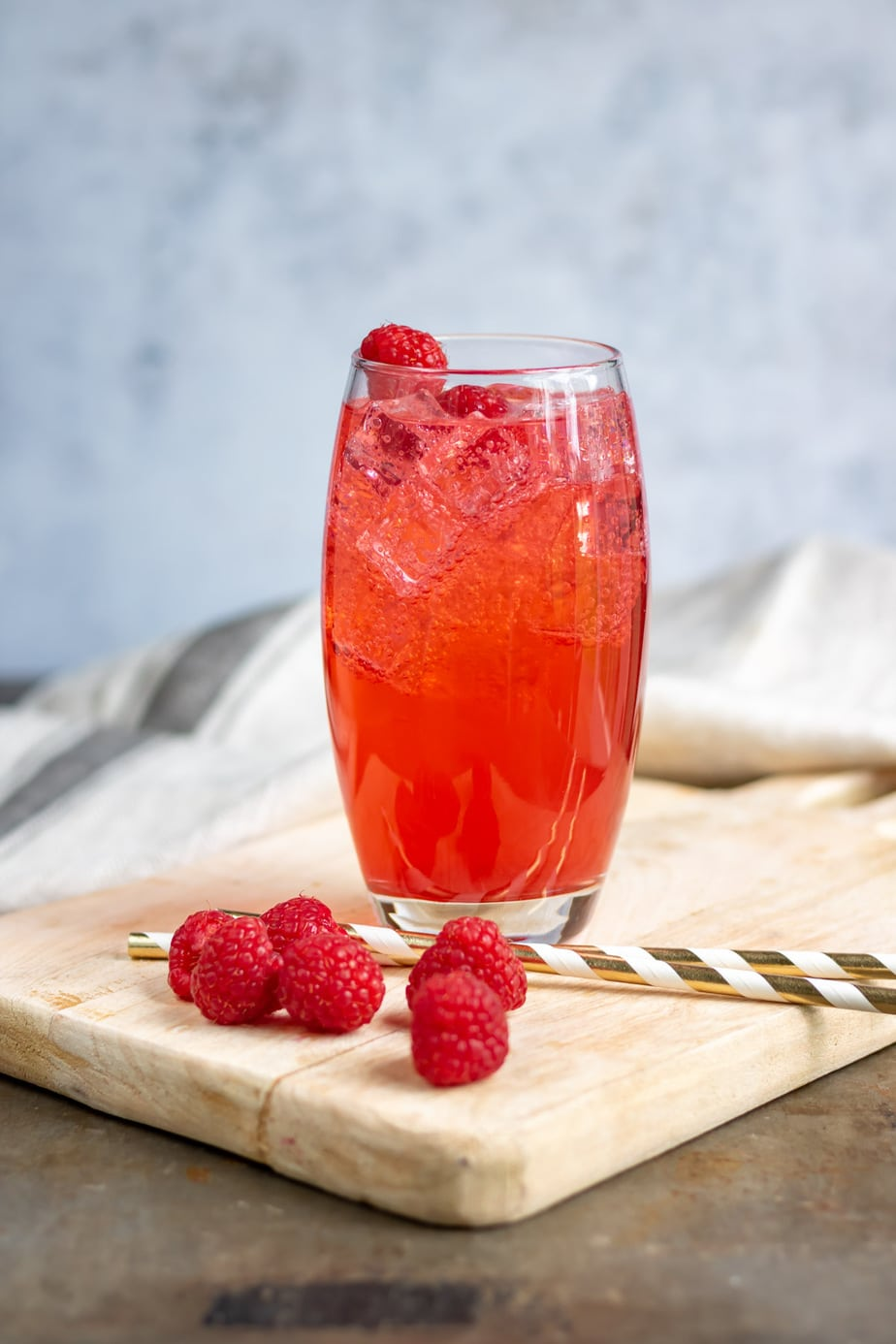Glass of raspberry soda with raspberries in it.