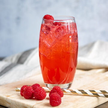 Glass of soda with raspberries and straws.