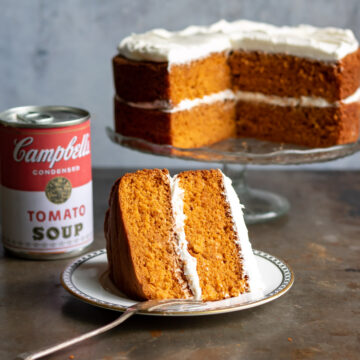 Cake on cake stand, can of soup and slice of cake with fork.