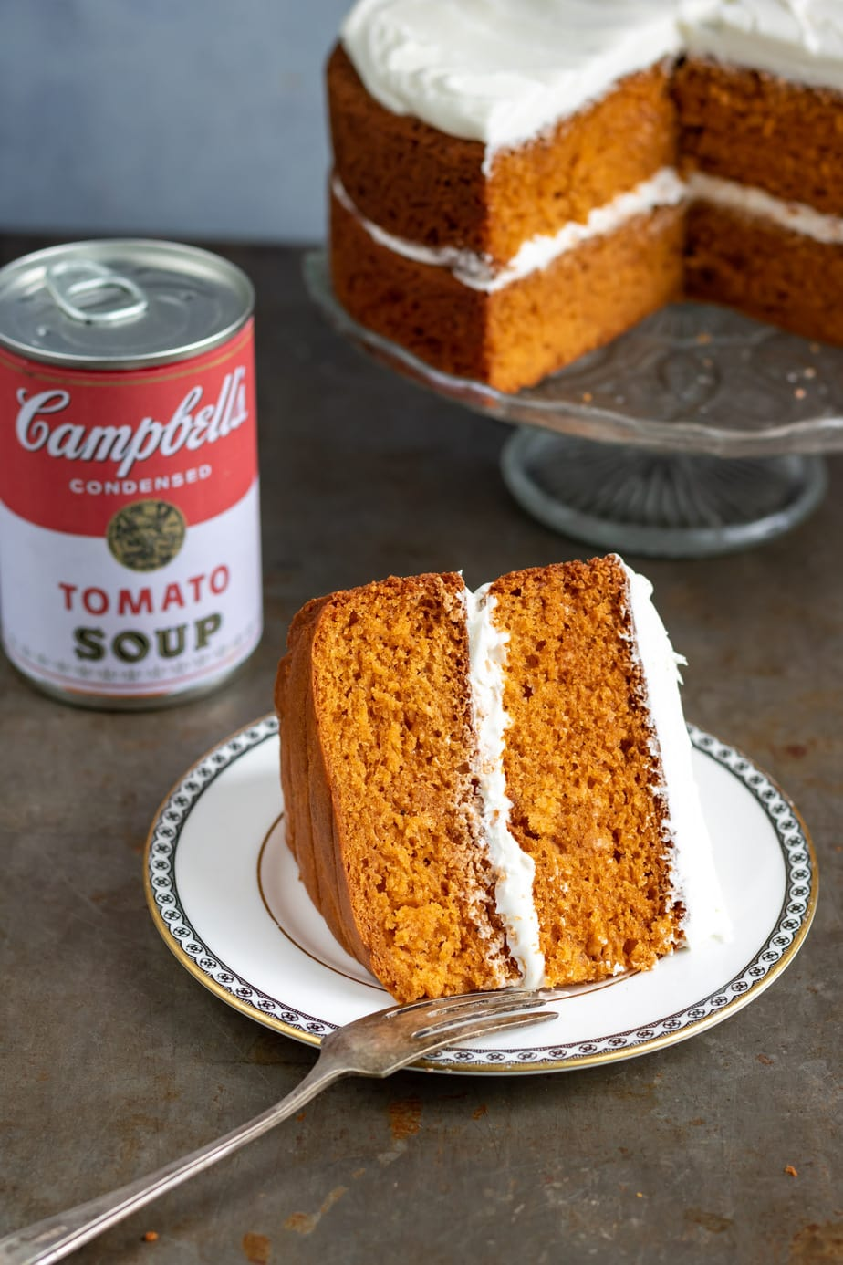 Slice of cake next to can of tomato soup.