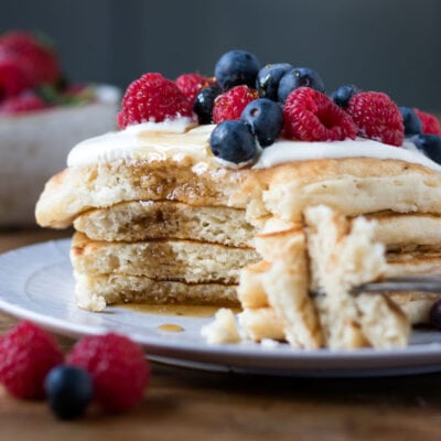 Stack of pancakes with a bite out.