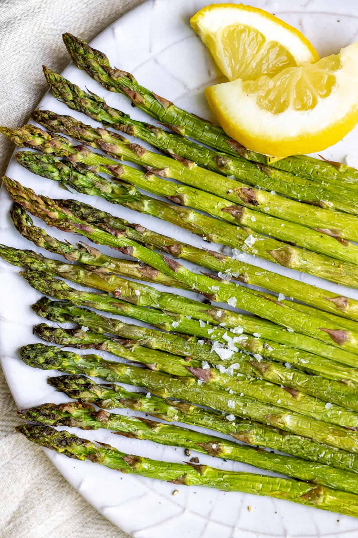 A plate of asparagus with a lemon wedge.