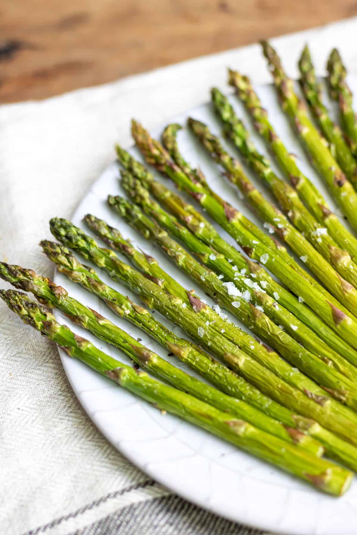 A plate of asparagus on a table.