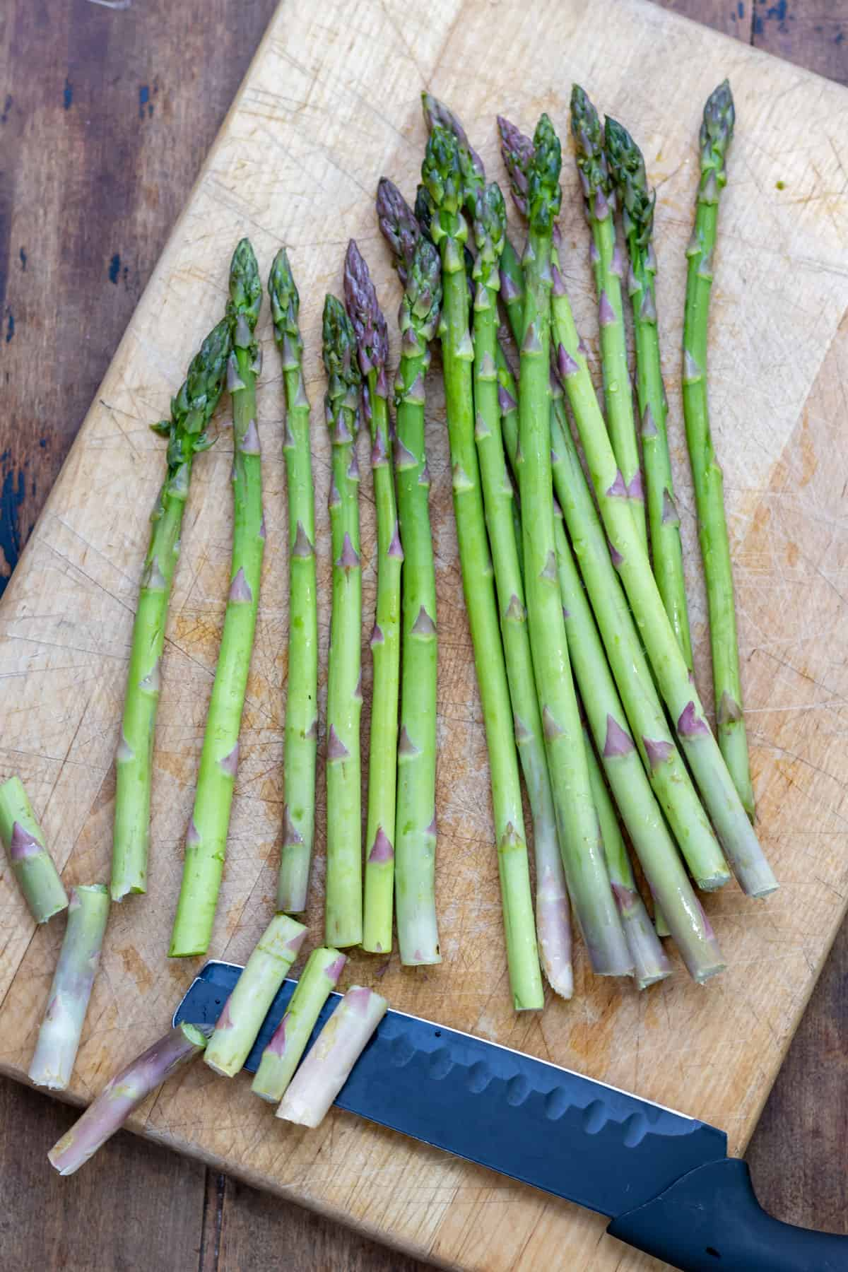 Trimming asparagus on a wooden cutting board.