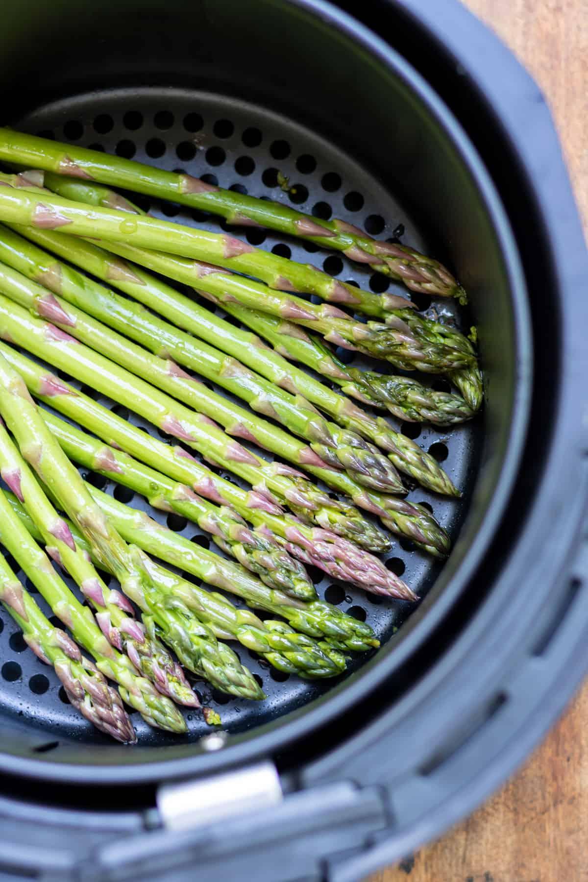 Asparagus in an air fryer basket.