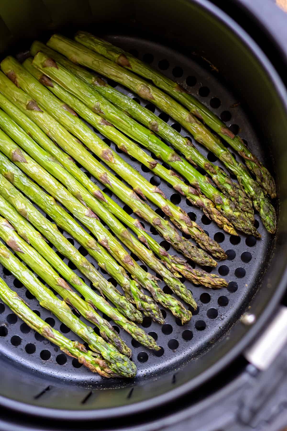 Cooked asparagus in an air fryer basket.