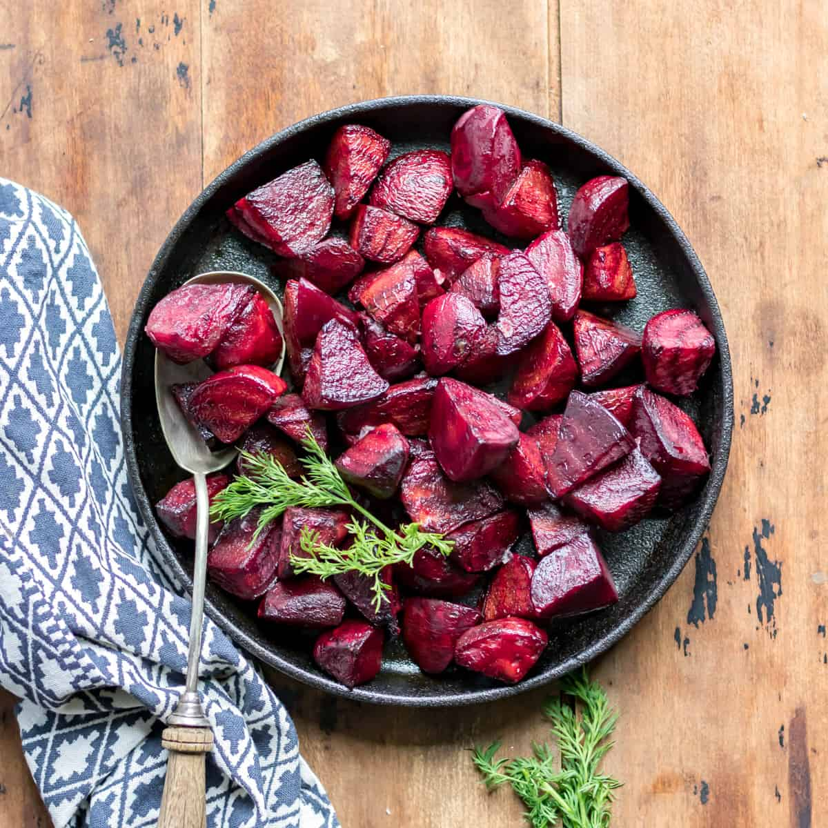Serving dish of beets on a wooden table.