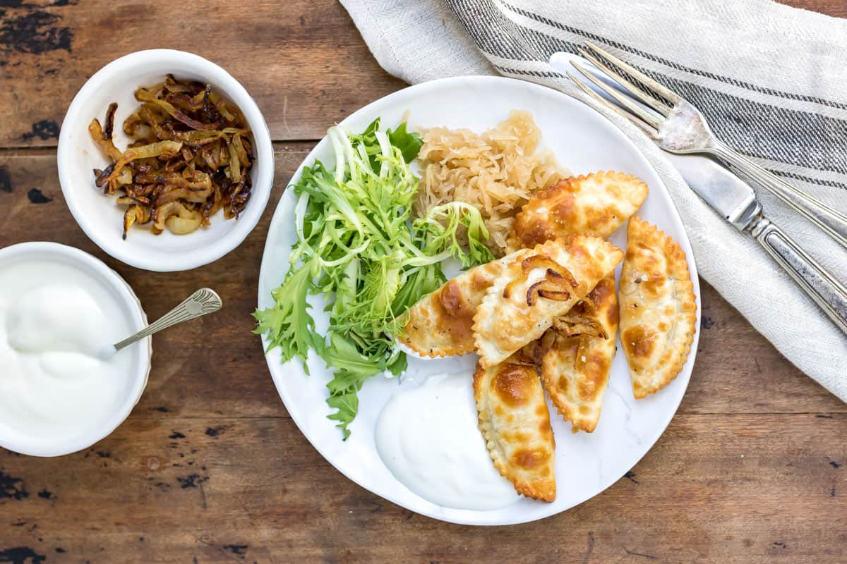 Plate of air fried pierogies on a table, with salad.