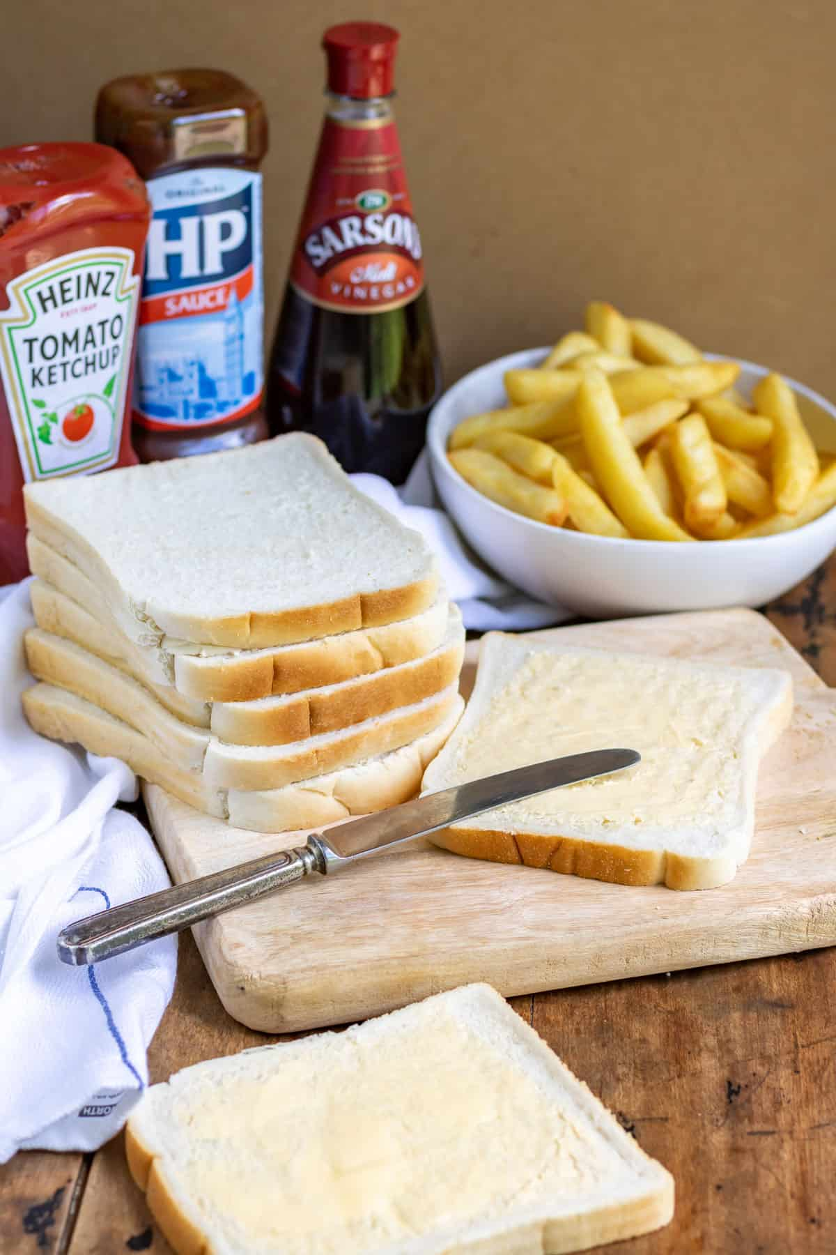 Stack of bread with a slice being buttered, in front of a bowl of fries.