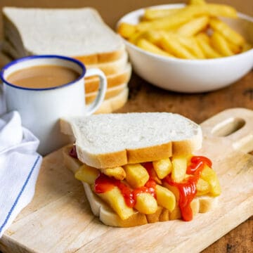 Table with a chip butty, mug of tea, bowl of fries.
