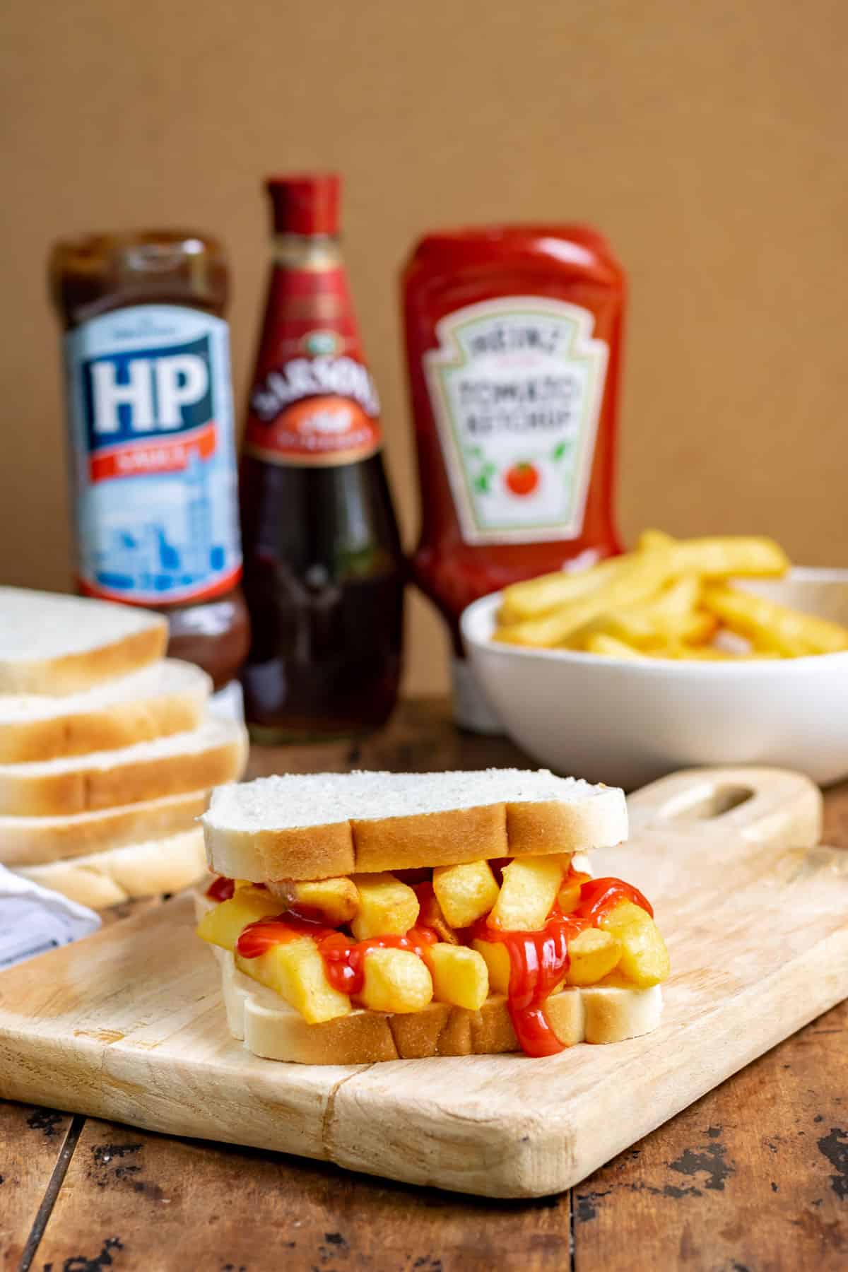 Table with chip butty, bowl of chips, ketchup and HP sauce bottles.