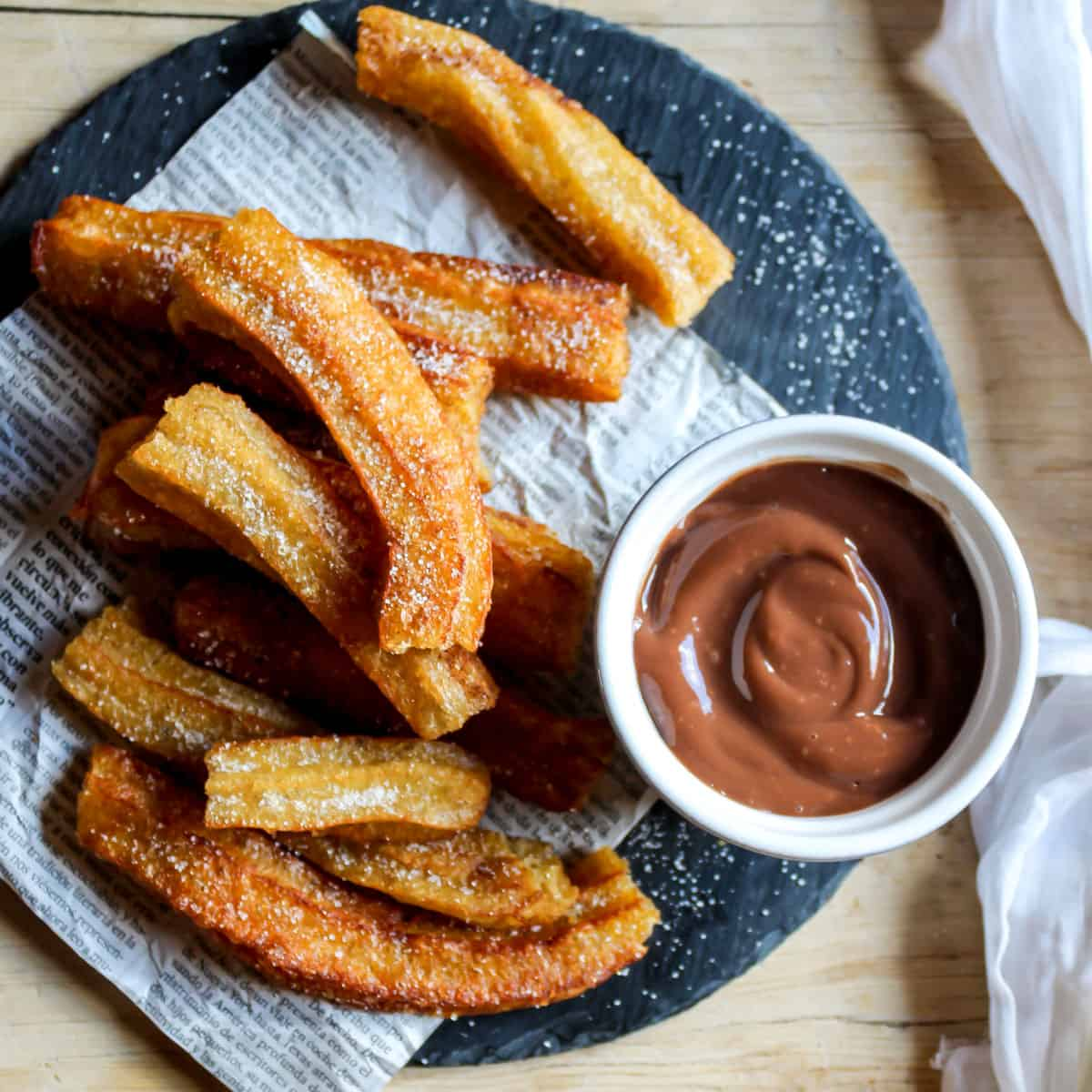 Looking down at a plate of churros and chocolate dipping sauce.