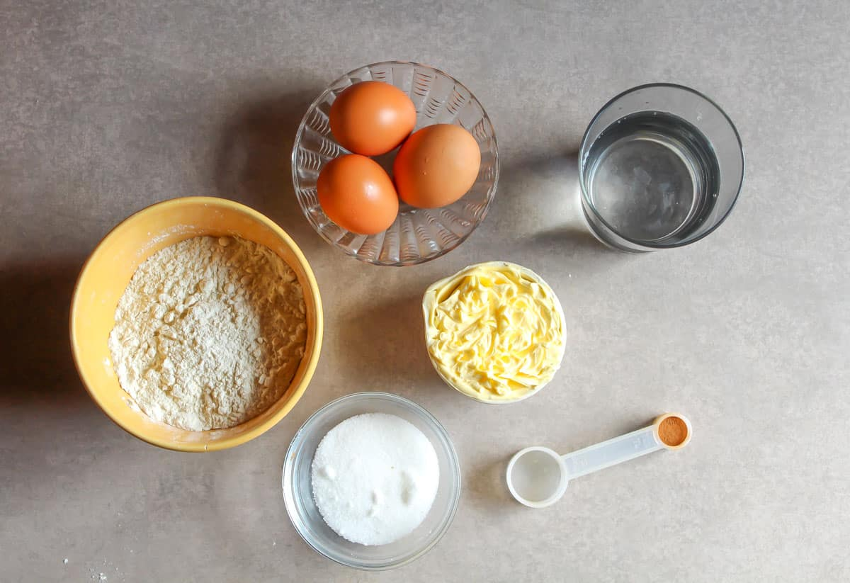 Ingredients on a table: eggs, flour, butter, sugar, cinnamon.