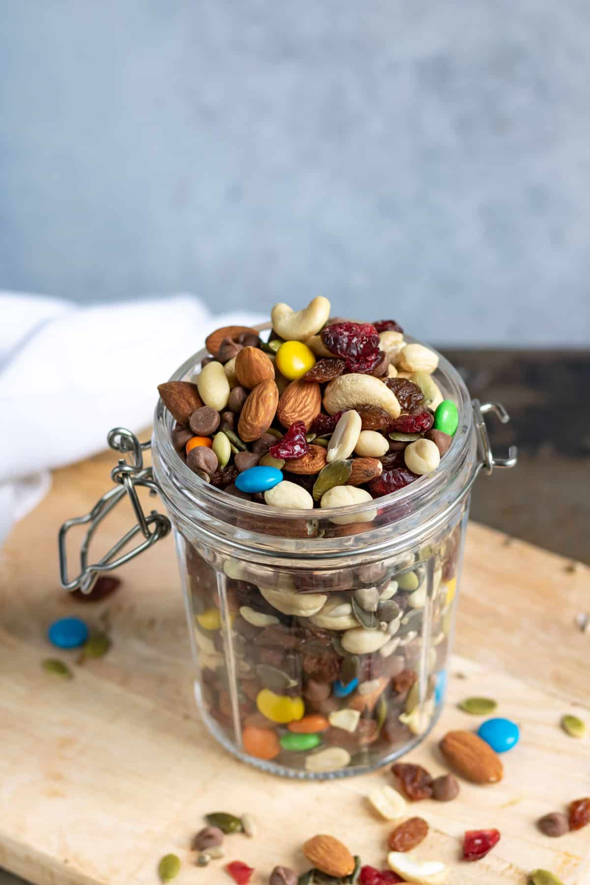A jar of trail mix on a wooden board.