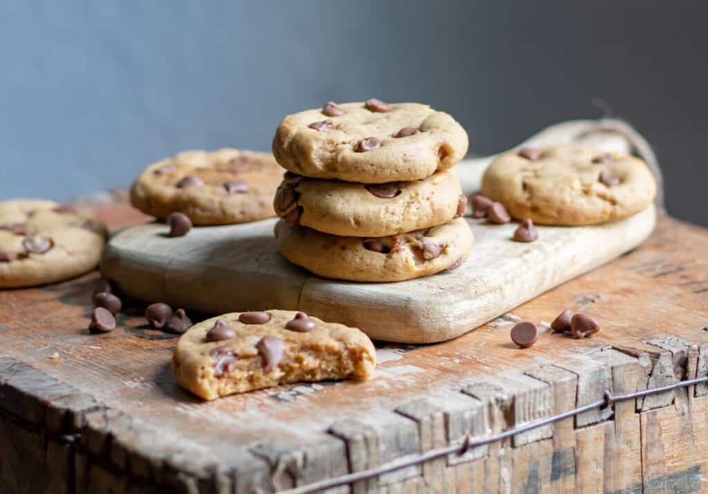 Stack of cookies with a cookie with a bite out in front.