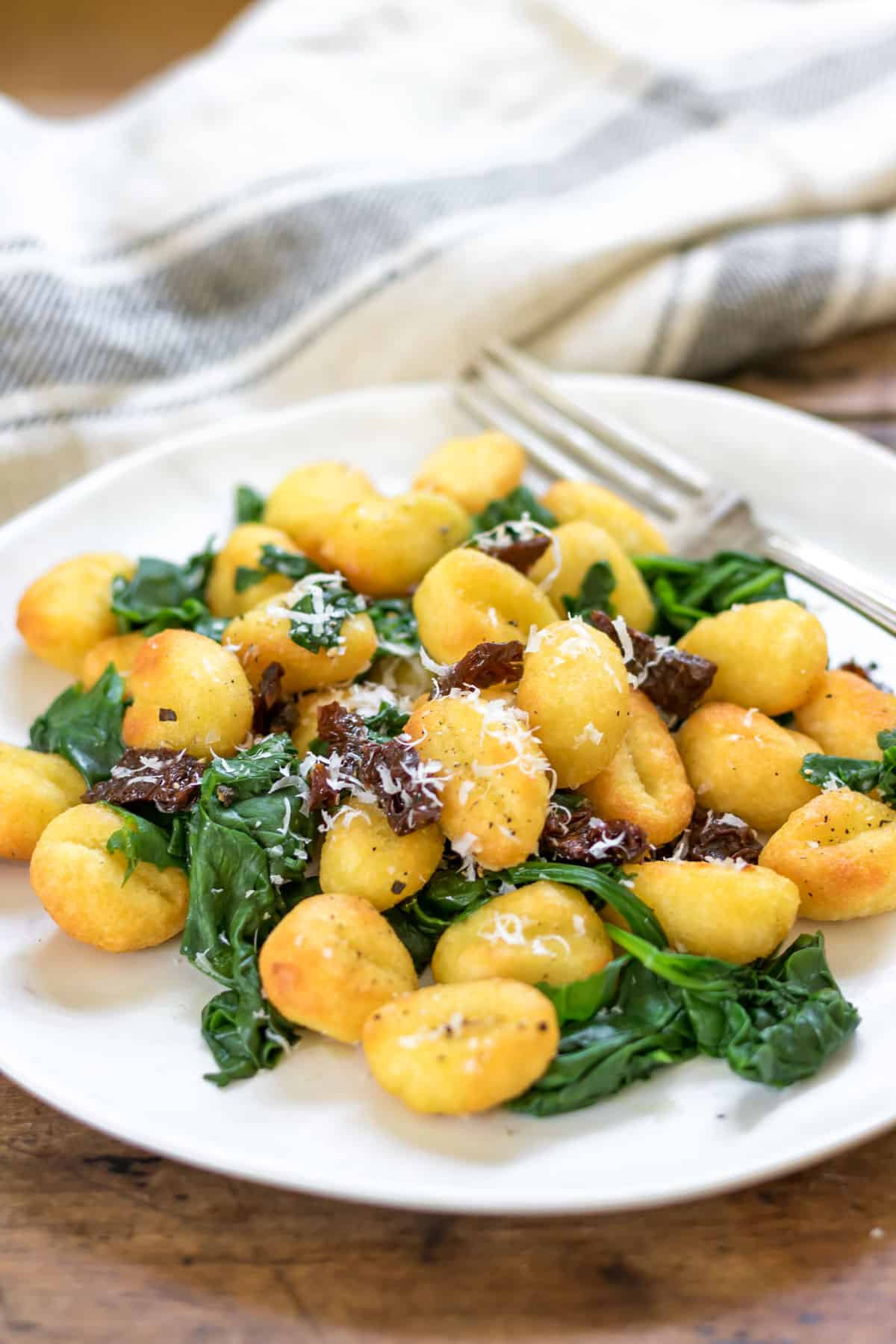 Plate of gnocchi with spinach, parmesan and sun dried tomatoes.