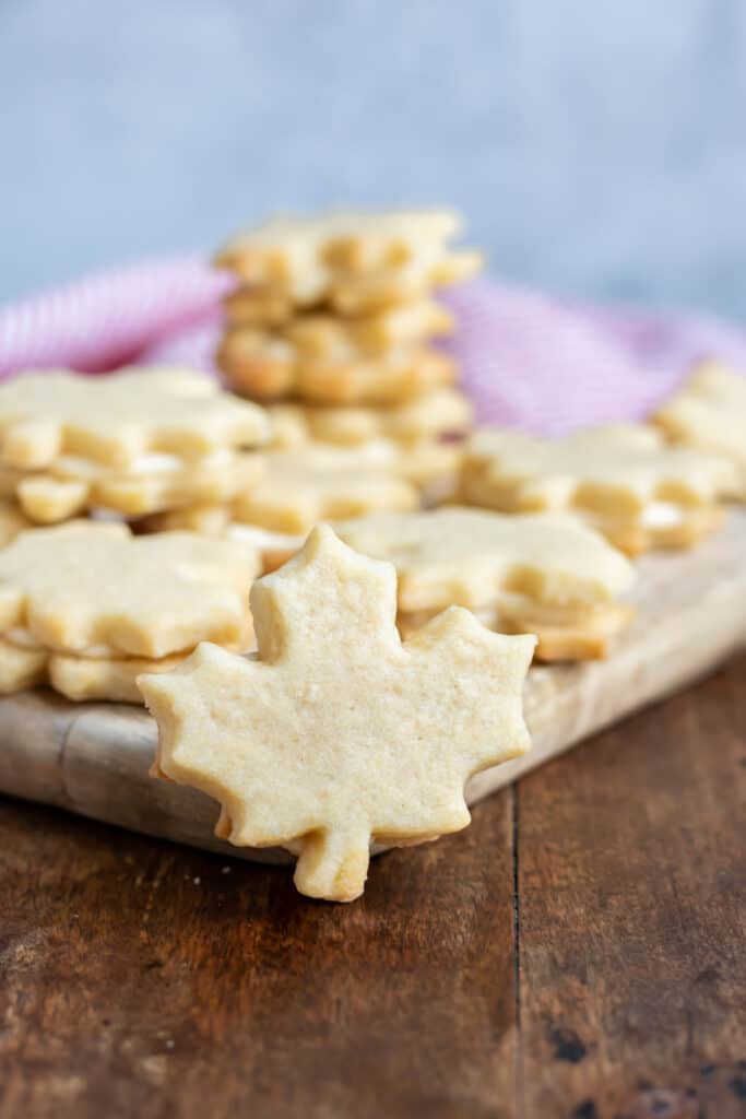 Maple leaf shaped cookie in front of more of them.