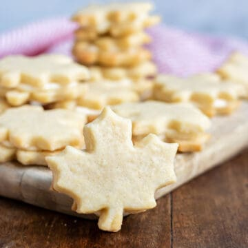 Maple leaf shaped cream cookie on a table in front of more cookies.