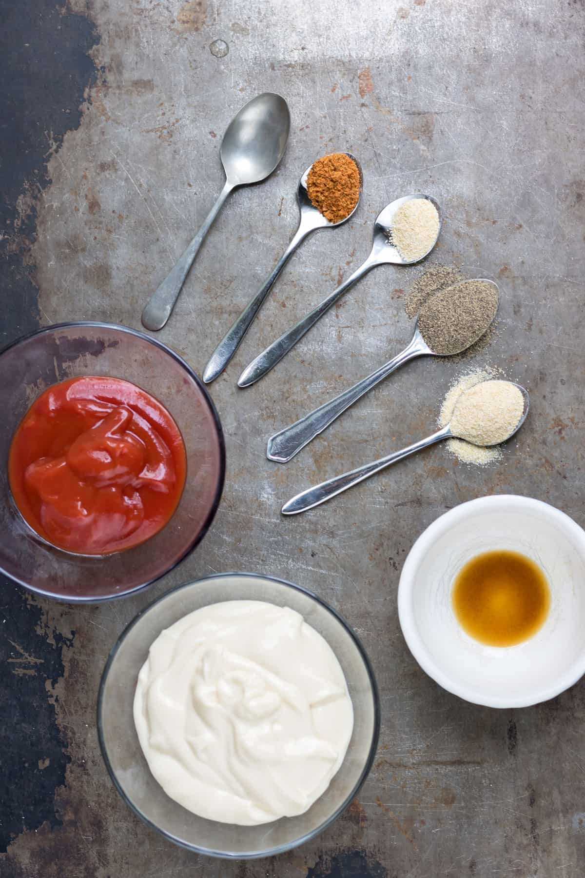 Ingredients on a table in bowls and on spoons.