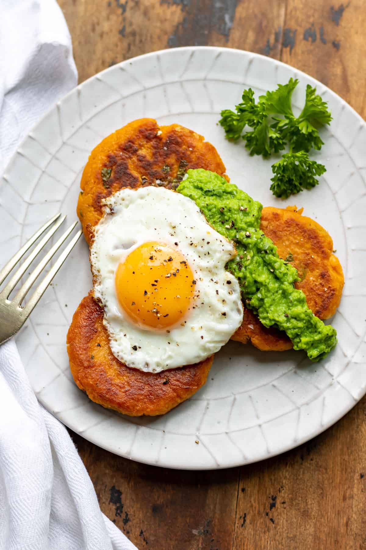 Plate of sweet potato patties topped with pea puree and a fried egg.