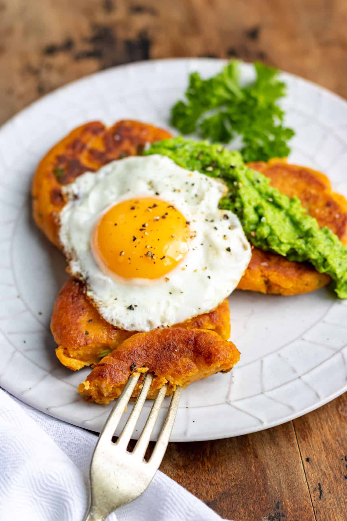 Plate of patties topped with an egg and pea puree.