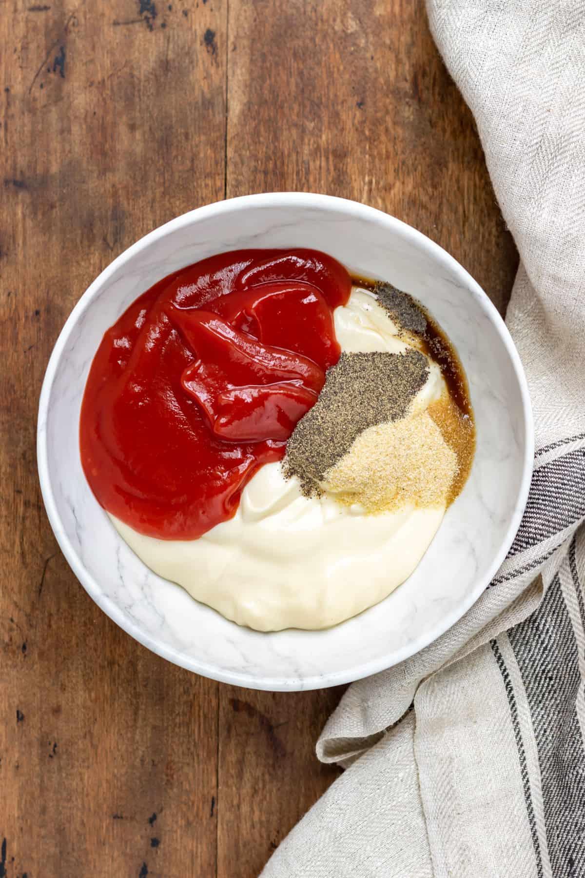 Bowl of mayo, ketchup, garlic powder, vinegar, worcestershire sauce and pepper.