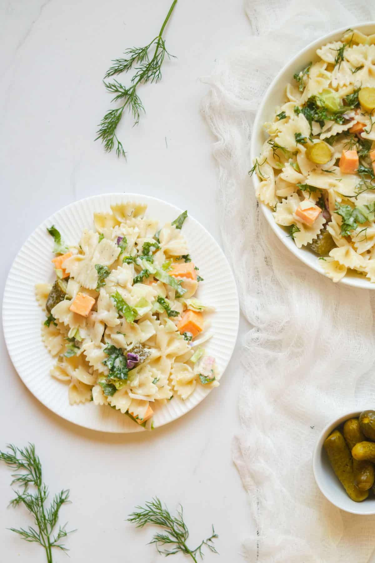 Table with plates of dill pickle pasta salad.