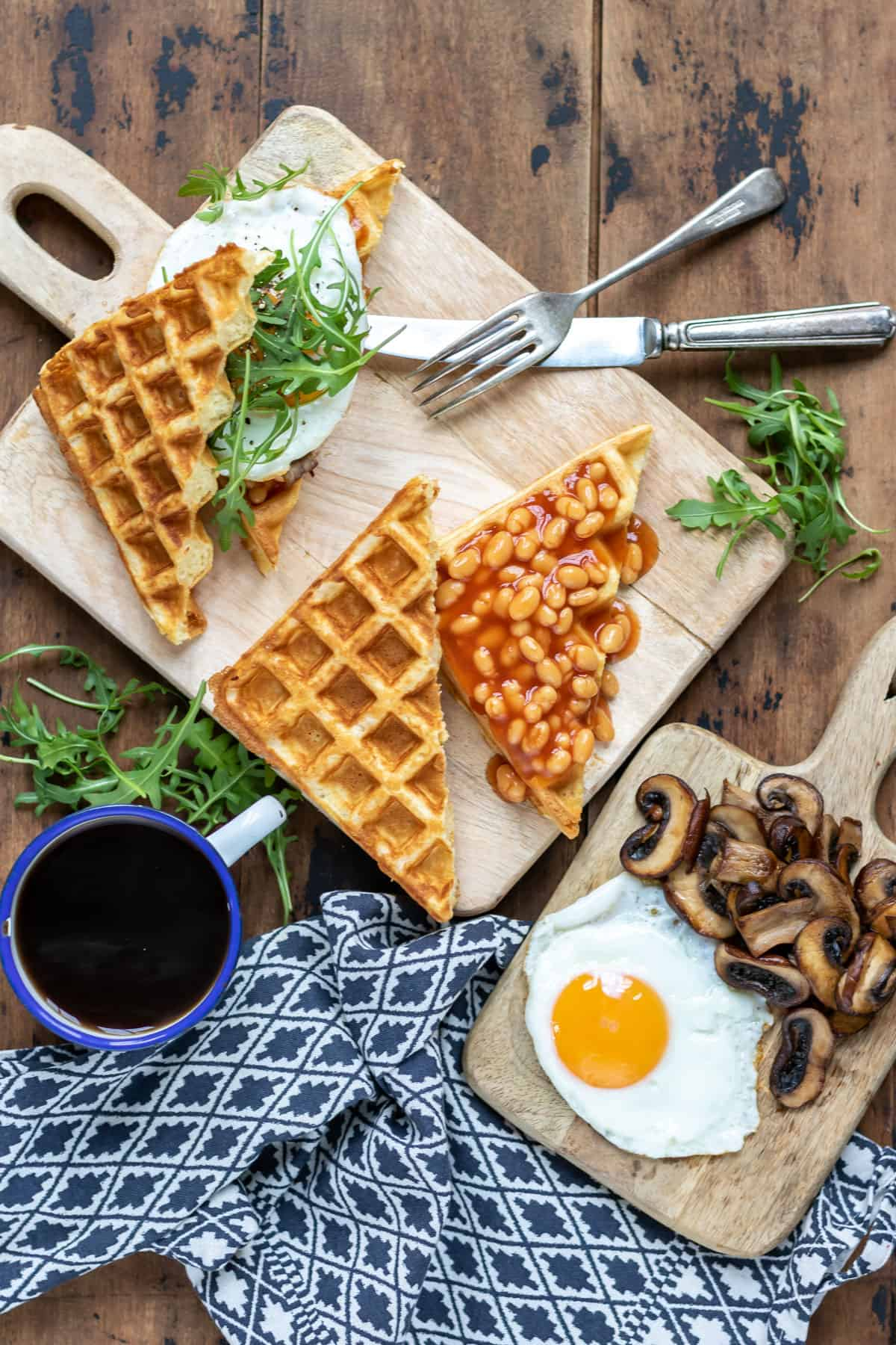 Waffles being topped with baked beans, mushrooms and eggs.