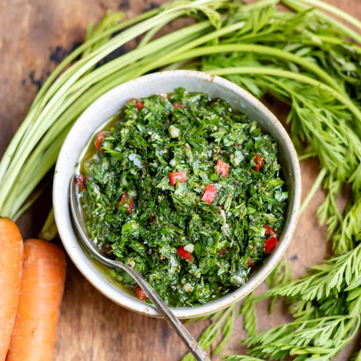 Bunched carrots around a bowl of chimichurri.