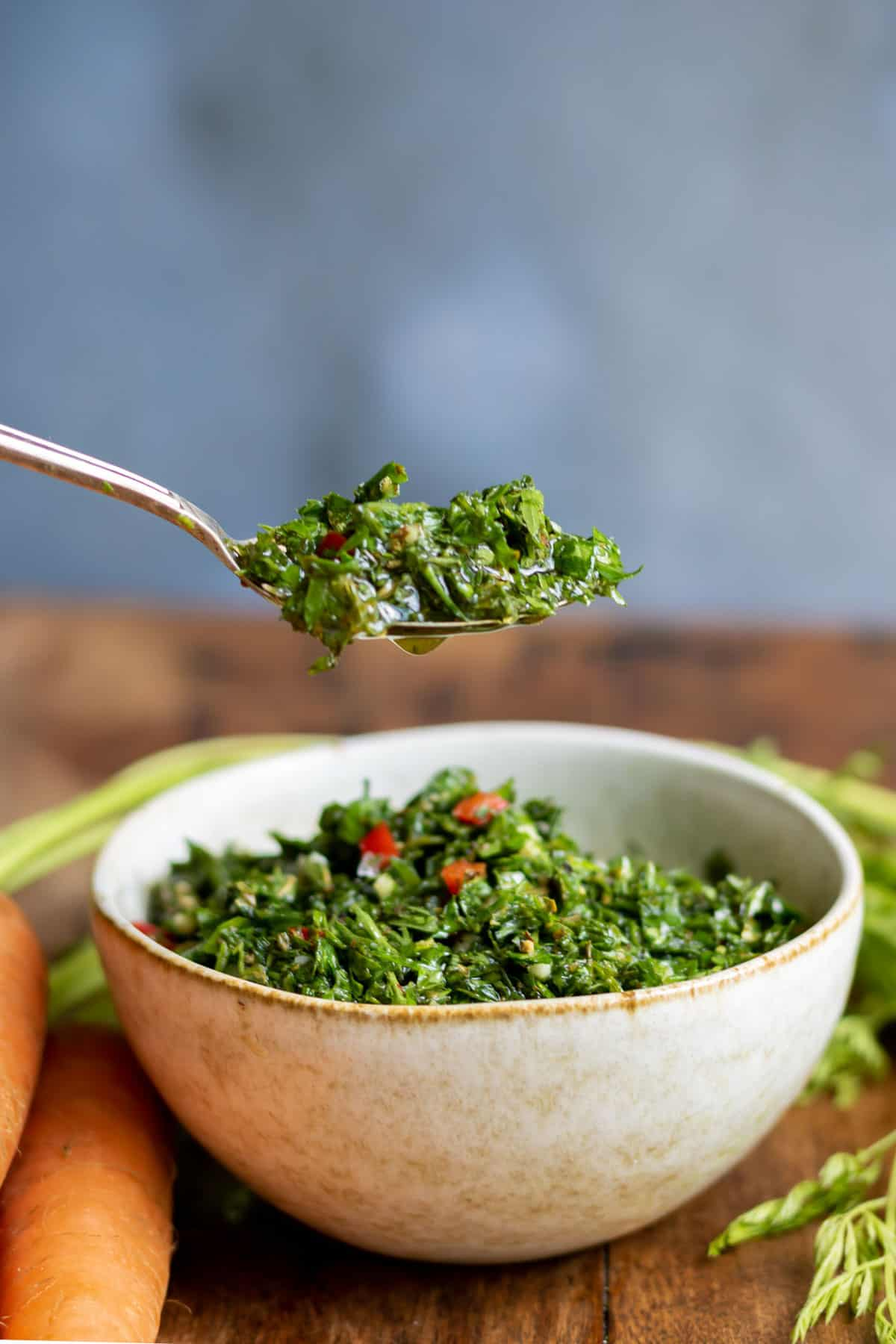 Spoon coming out of a bowl of chimichurri.