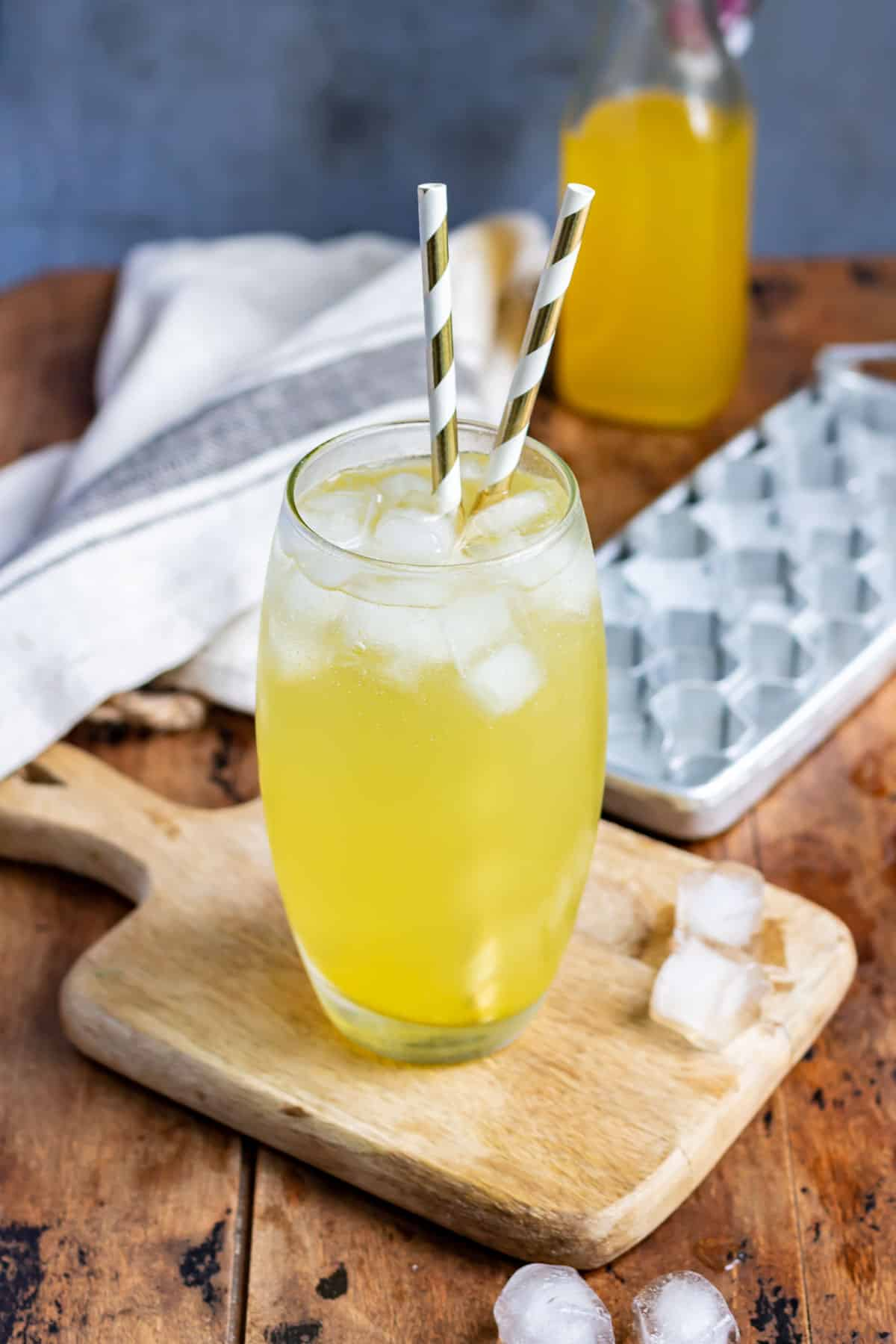 Table with ice and a glass of soda with mango syrup.