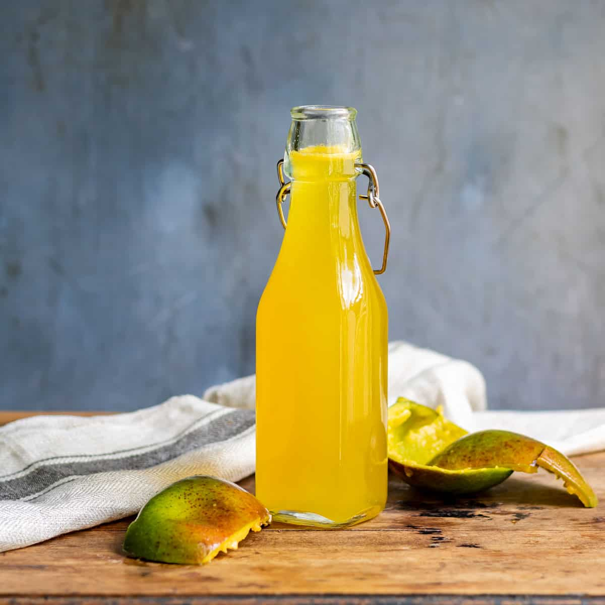 Table with bottle of syrup and mango peelings.