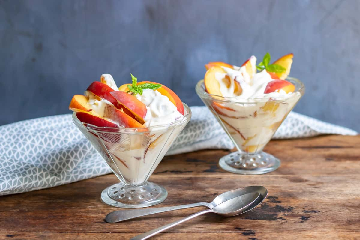 Dishes of peaches and cream topped with a sprig of mint.