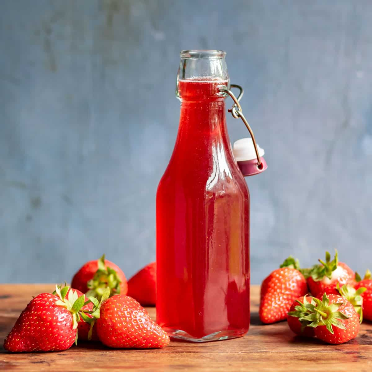 Bottle of strawberry syrup on a wooden table.