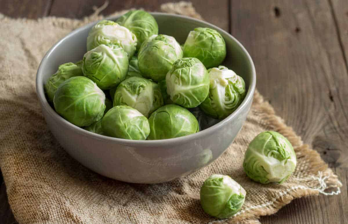 Brussels Sprouts in a bowl on an old wooden table.