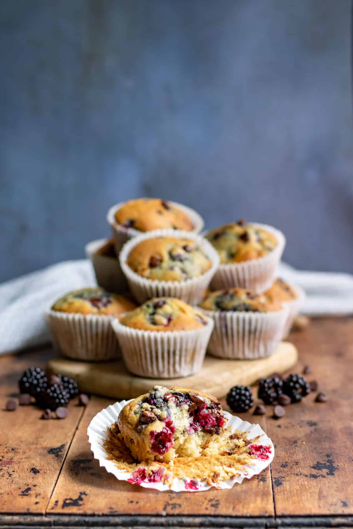 A pile of muffins with one in front with a bite out.