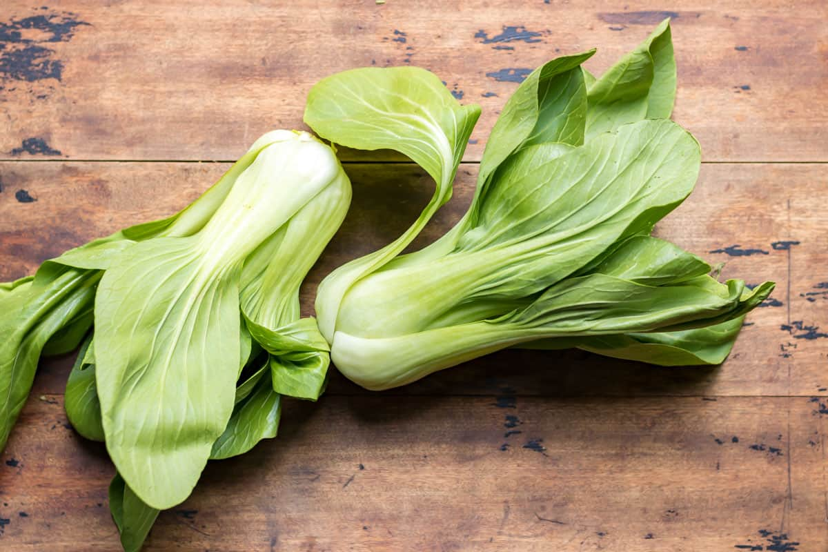 Two bok choi on a wooden table.