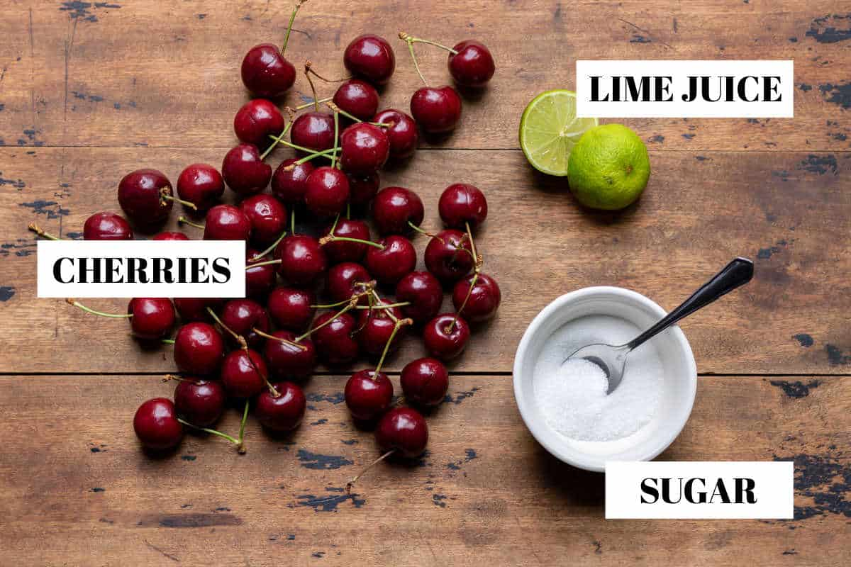 Cherries, lime and sugar on a table.