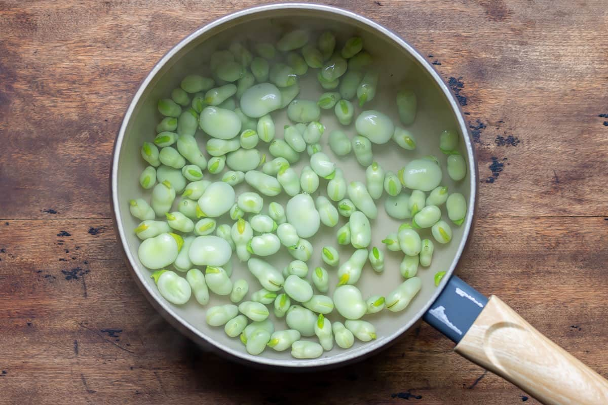 Blanching fresh fava beans.
