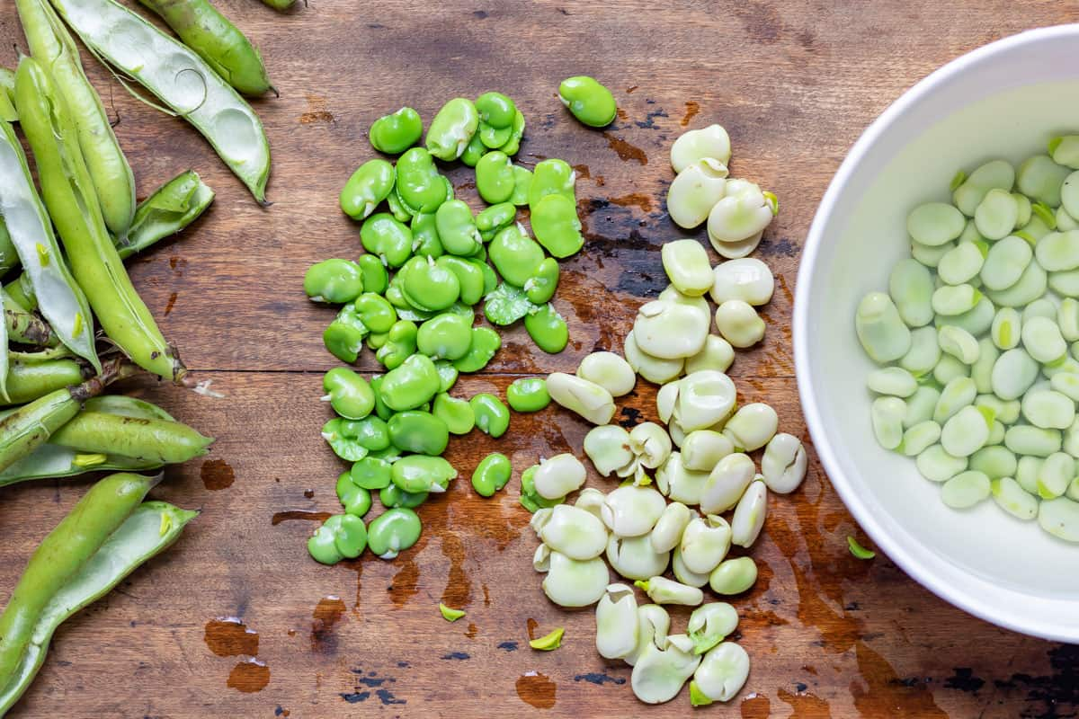 Prepping broad beans by squeezing out of the skins.