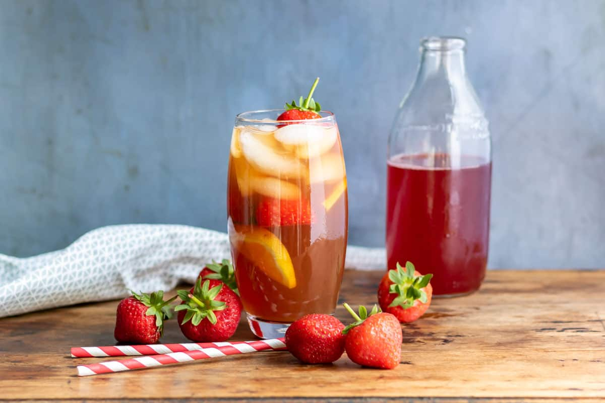 Table with a glass of iced tea, pitcher and bottle of strawberry syrup.