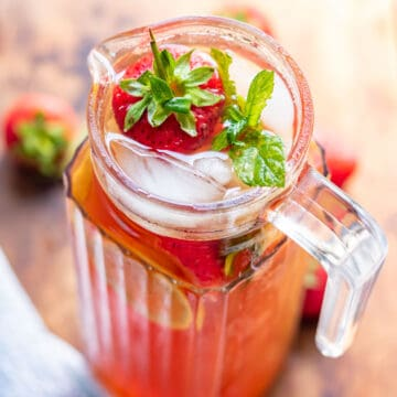 Pitcher of iced tea with strawberries.